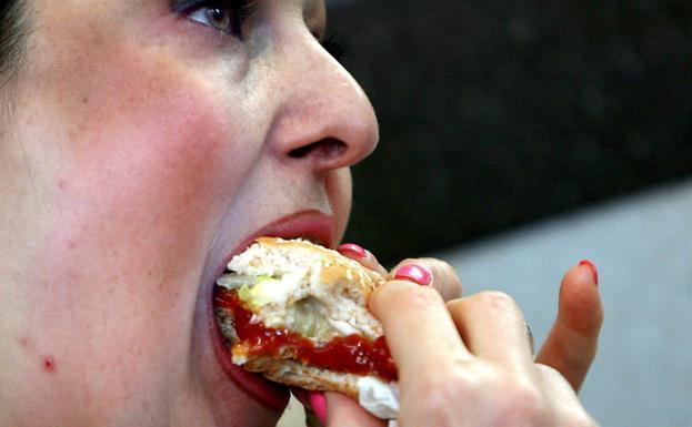 A woman eats a hamburger in London.
