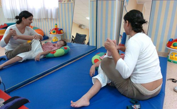 A monitor attends to a child in an Early Care center in Lorca, in a file photo.