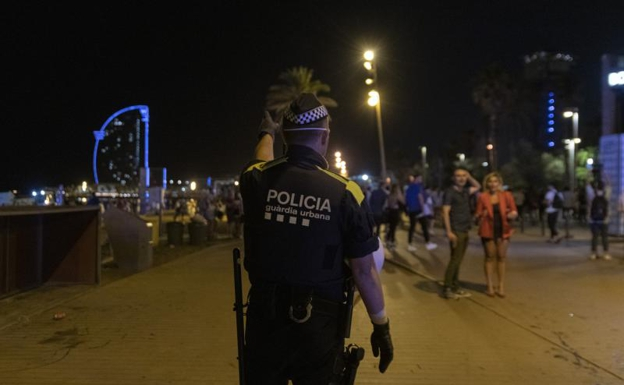 An agent of the Urban Guard evicts the Barceloneta beach.