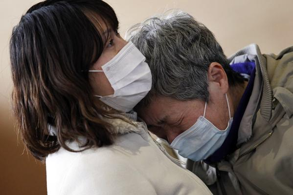 A woman and her maternal aunt cry at a shelter as they reunite for the first time after an earthquake and tsunami in Rikuzentakata in Iwate prefecture.