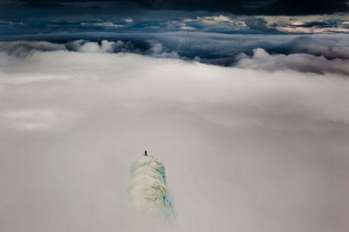 Một nhà leo núi đang đứng trên đỉnh một ngọn núi ở Iceland. Chẳng còn gì ngoài con người bé nhỏ trước thiên nhiên hùng vĩ.