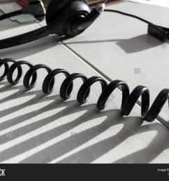 customer service call center abstract spiral cord in sunshine at office cubicle workplace with headset in [ 1500 x 1245 Pixel ]