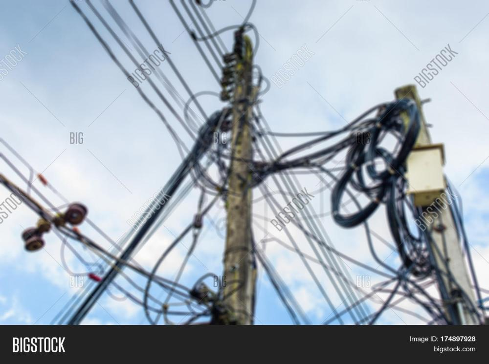 medium resolution of blurred high voltage power pole with wires tangled wire and cable clutter potential danger