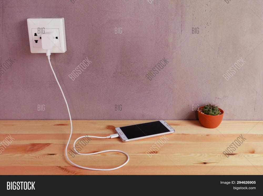 medium resolution of plug in power outlet adapter cord charger of mobile phone on wooden floor