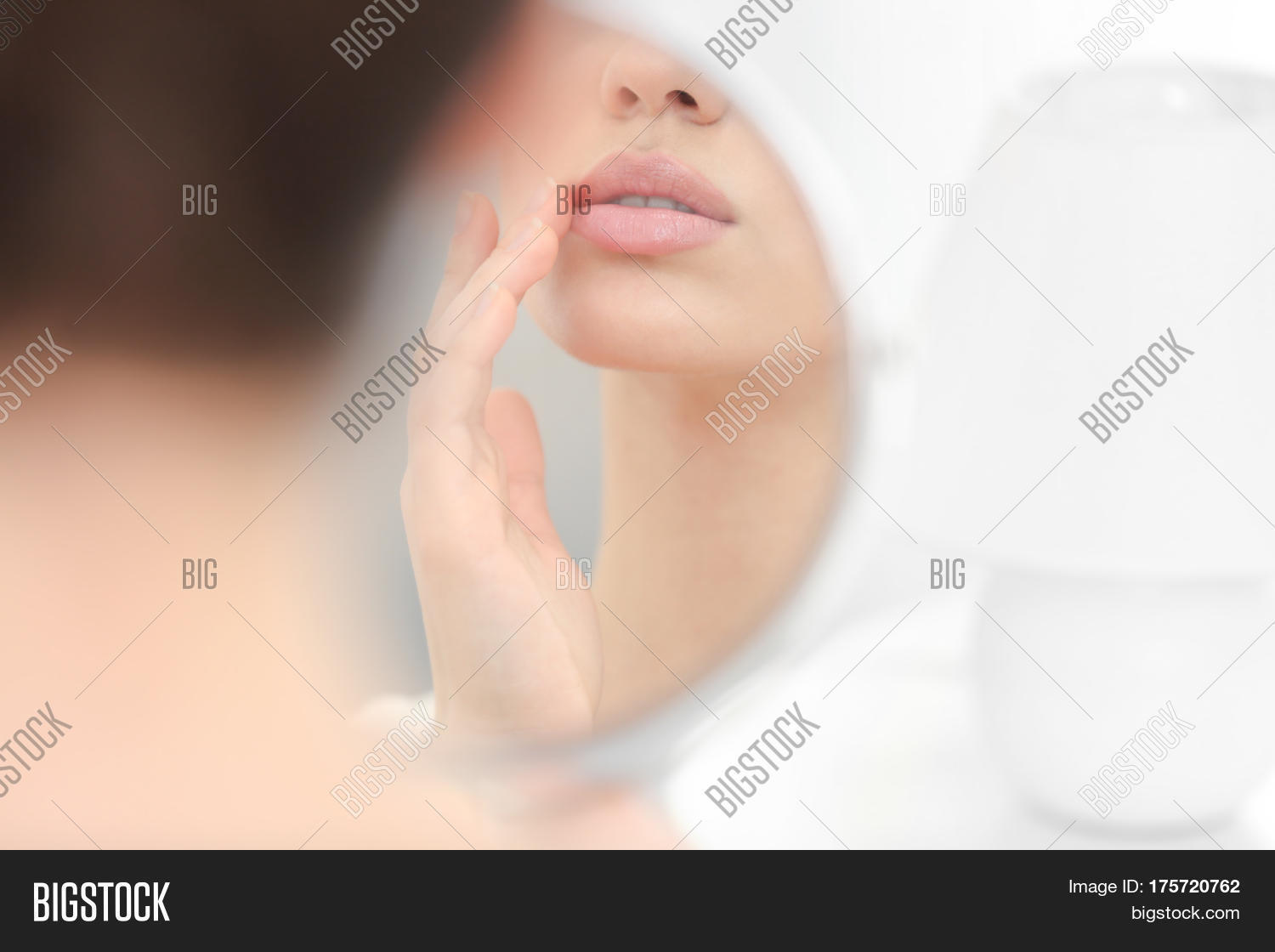 hight resolution of young woman with cold sore looking in mirror at home