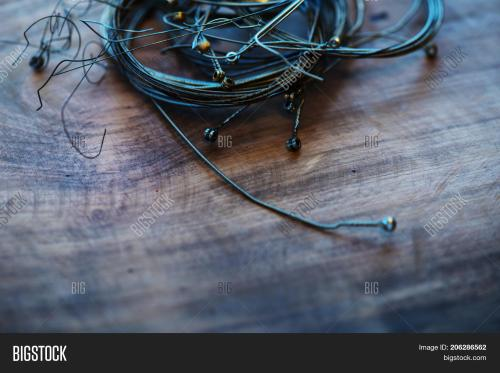 small resolution of old guitar strings on grungy old wooden desk ball end coiled and