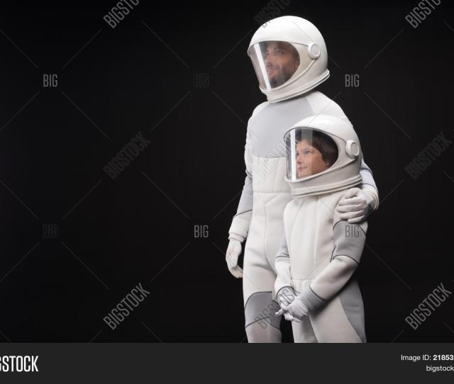 Inseparable Cheerful Father And His Interested Son Wearing White Helmet With Full Armor Are Standing