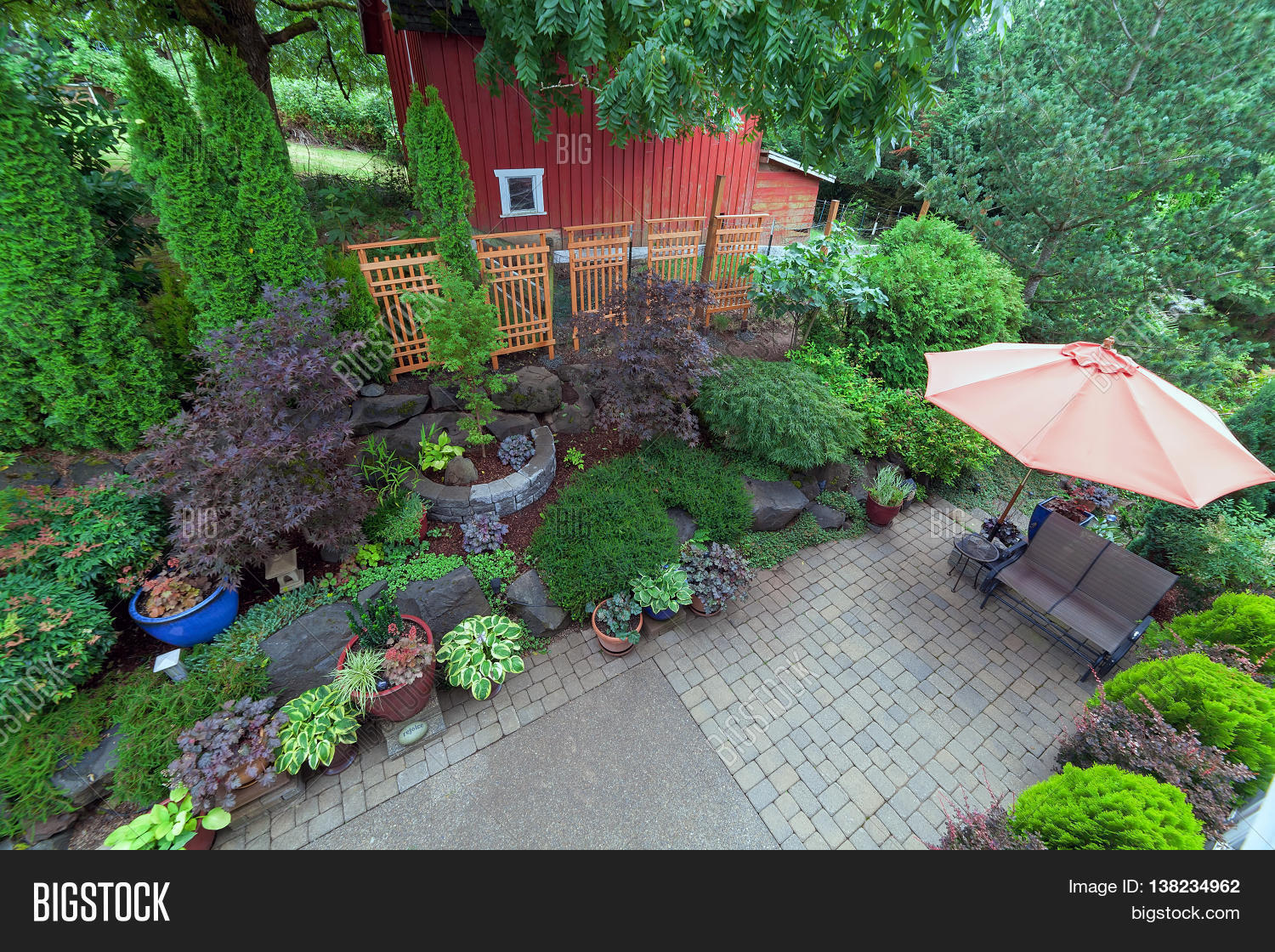 Backyard garden landscaping with paver bricks patio hardscape trees potted plants shrubs pond rocks furniture and red barn Stock Photo & Stock ...