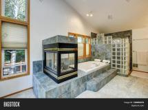 Master Bathroom Interior With Tile Flooring And Fireplace