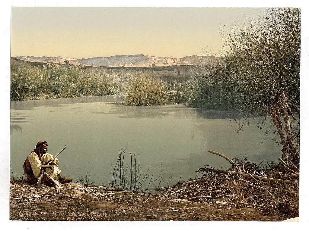 A man sits by the River Jordan