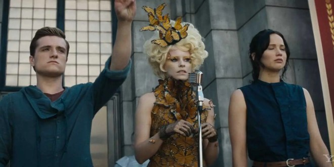 Peeta Mellark (Josh Hutcherson) and Katniss Everdeen (Jennifer Lawerence) on stage with Effie Trinket (Elizabeth Banks), soon after their selection as tributes