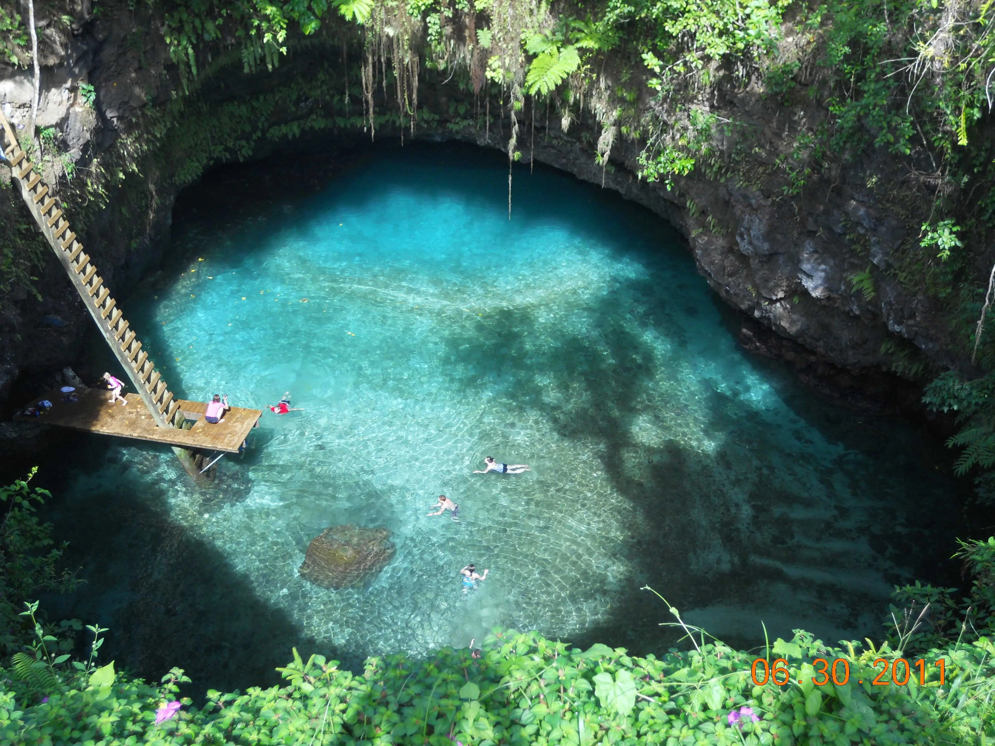 Swim in the To Sua Ocean trench, a 30-meter deep natural seawater pool surrounded by stunning gardens in the village of Lotofaga in Samoa.