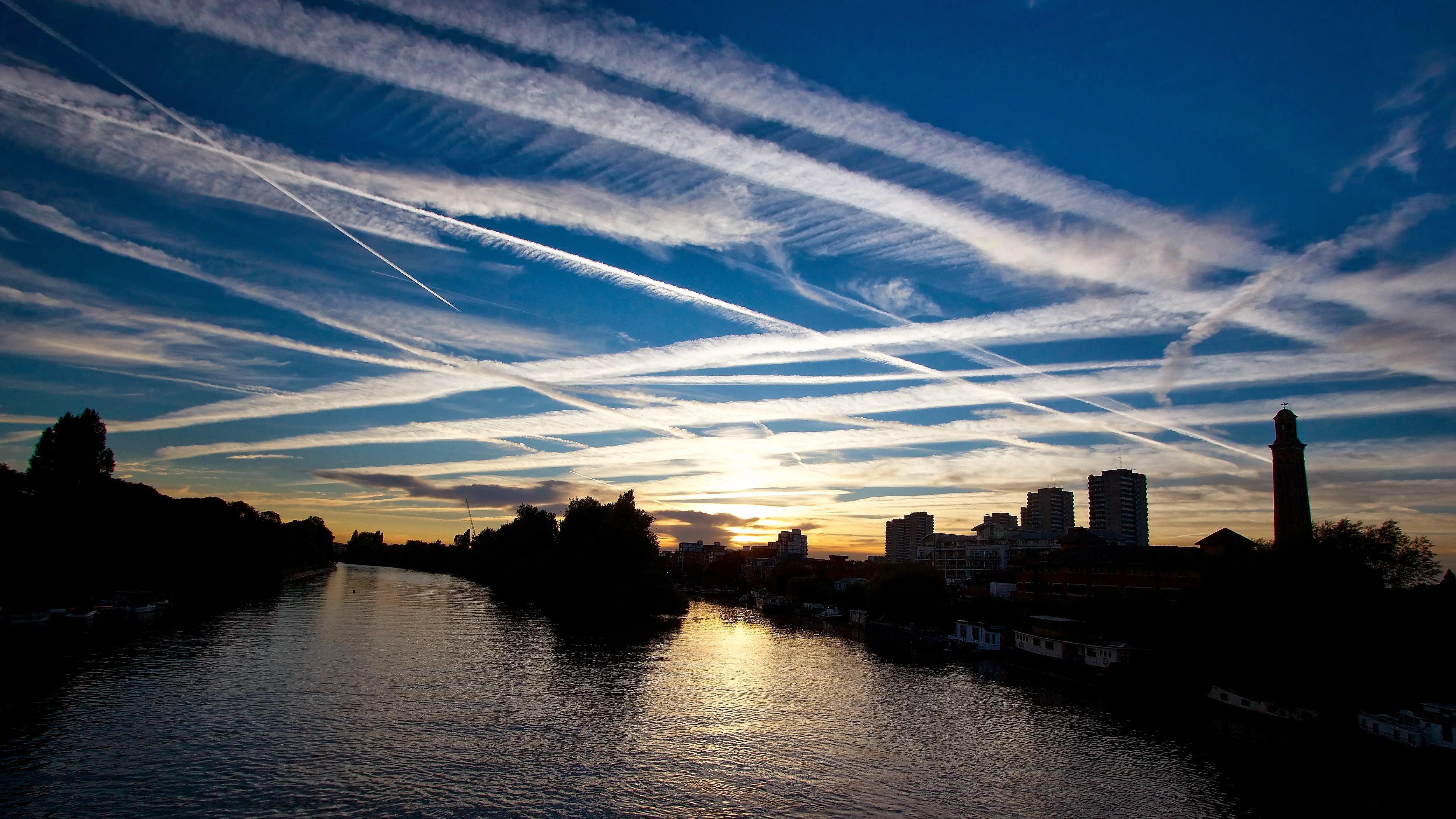 Globalized transportation networks, especially commercial aviation, are a major contributor of air pollution and greenhouse gas emissions, like the chem-trails seen here in the west London sky over the River Thames.