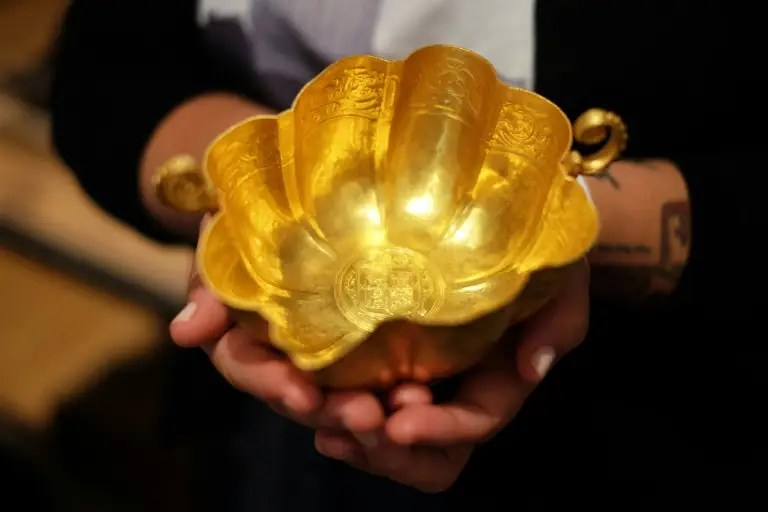 An employee shows a Spanish gold chalice at the Guernsey's in New York on July 6, 2015