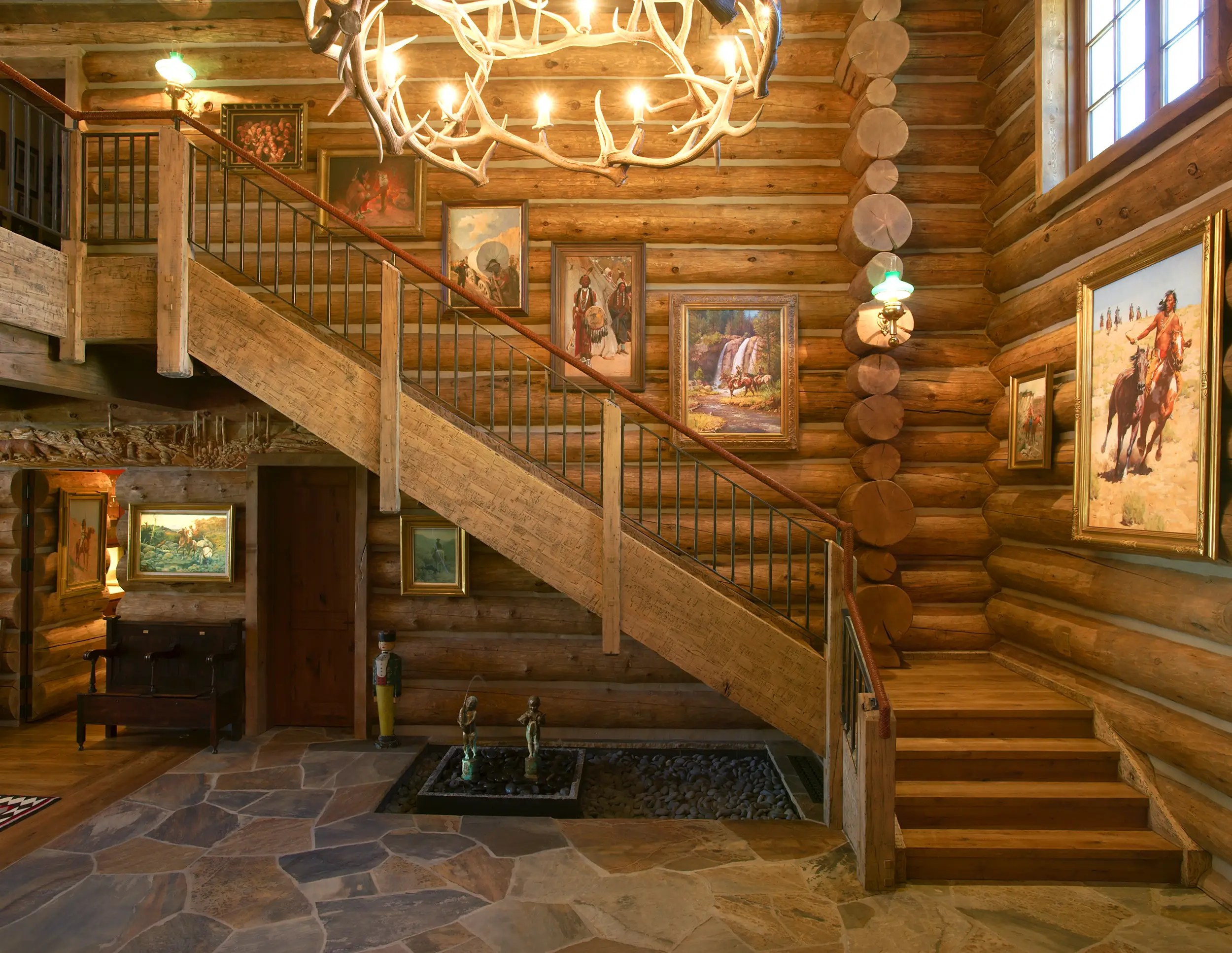 An antler chandelier keeps the theme going strong, while banisters are wrapped in leather.