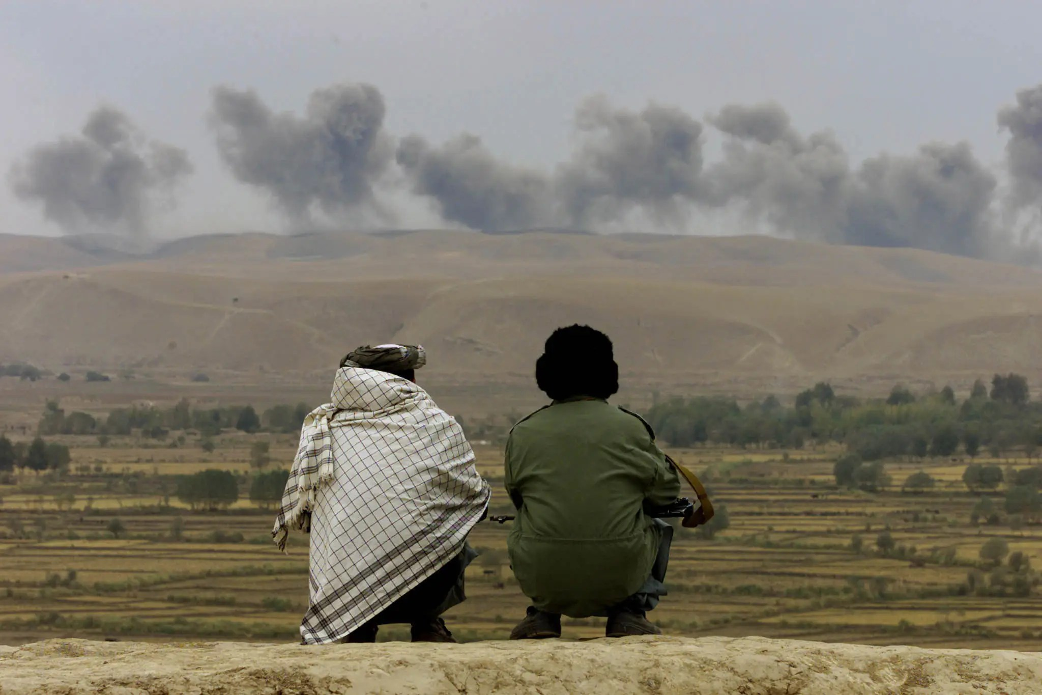 Two Northern Alliance soldiers watch as the dust and smoke rises after explosions in Taliban positions on Kalakata hill, near the village of Ai-Khanum in northern Afghanistan, November 1, 2001.