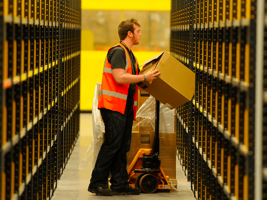A worker lifts a box at Amazon's new fulfillment centre after it was opened by Scotland's First Minister Alex Salmond in Dunfermline, Scotland, November 15, 2011.The warehouse covers more than one million square feet (93,000 square metres), about the size of 14 soccer pitches, and is Amazon?s biggest in the United Kingdom. It will create 750 permanent jobs, along with a further 1,500 temporary jobs during peak periods.
