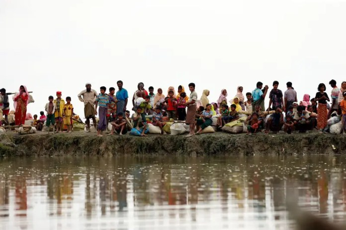 Rohingya refugees are seen waiting for a boat to cross the border through the Naf river in Maungdaw, Myanmar, September 7, 2017.REUTERS/Mohammad Ponir Hossain