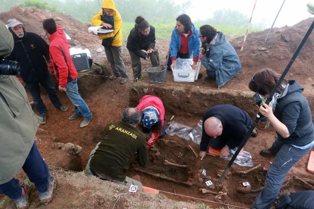 A la izquierda, el forense Francisco Etxeberría (con gorra y chubasquero) dirige la exhumación individualizada y anotada de los cuerpos para su traslado al laboratorio. / J. M. PARDO