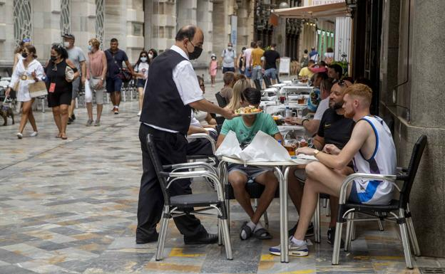 A waiter serves customers on a terrace in Cartagena, in August of this year.