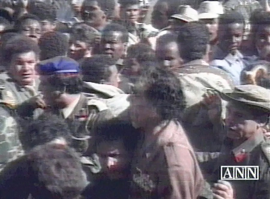 In this image released by Libyan television Qaddafi walks through a crowd after an alleged assassination attempt during a rally in Libya. Qaddafi said the alleged assailant, was an agent of the British intelligence and had confessed while the British government denied an assassination attempt,  Sept. 11, 1998