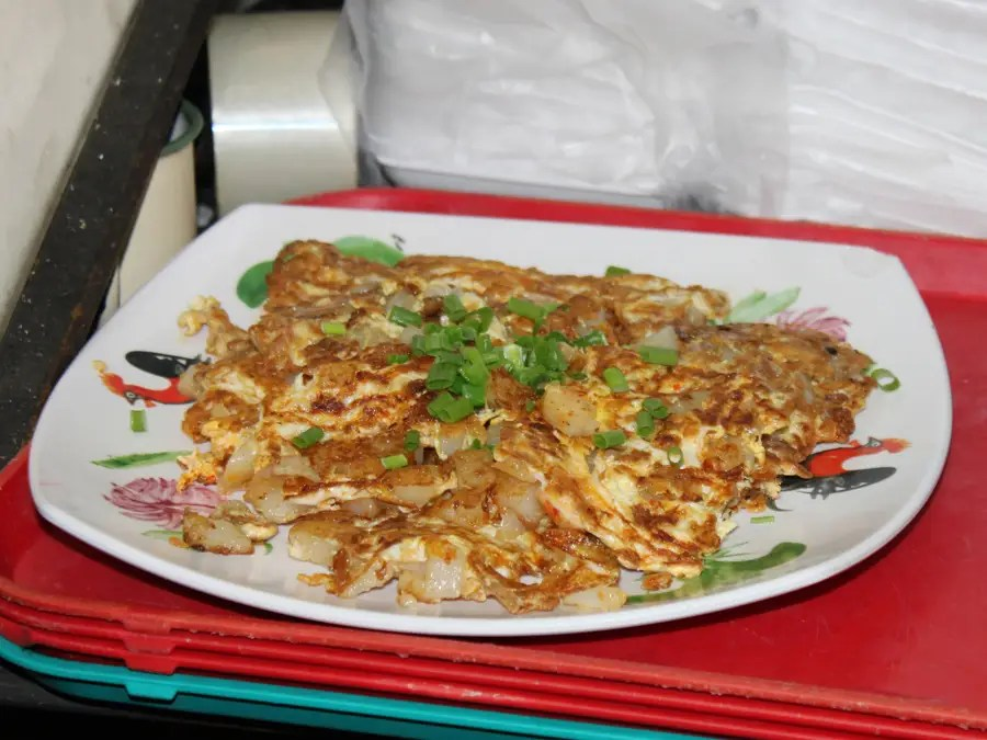 This Chinese seafood omelette is topped with chopped scallions.