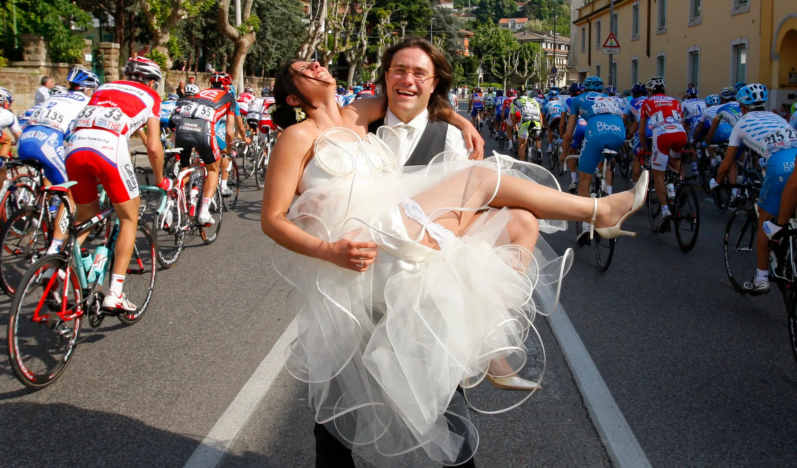 Cyclists ride past these newlyweds during the second stage of the Giro d'Italia in Italy.