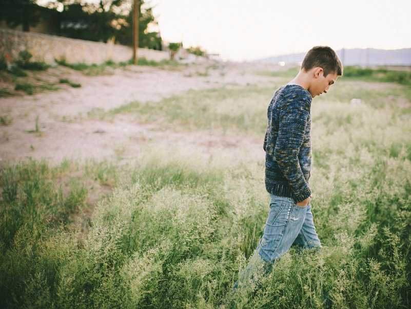 Teenage Boy Walking Through Field