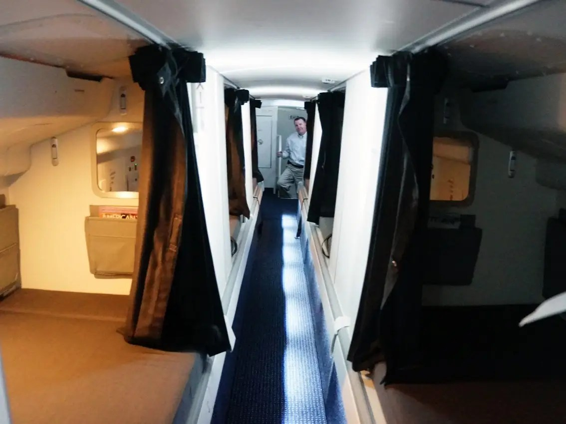 To get back out to the main cabin, an emergency exit under one of the beds leads straight into the cabin, through an overhead bin that's locked from the outside.