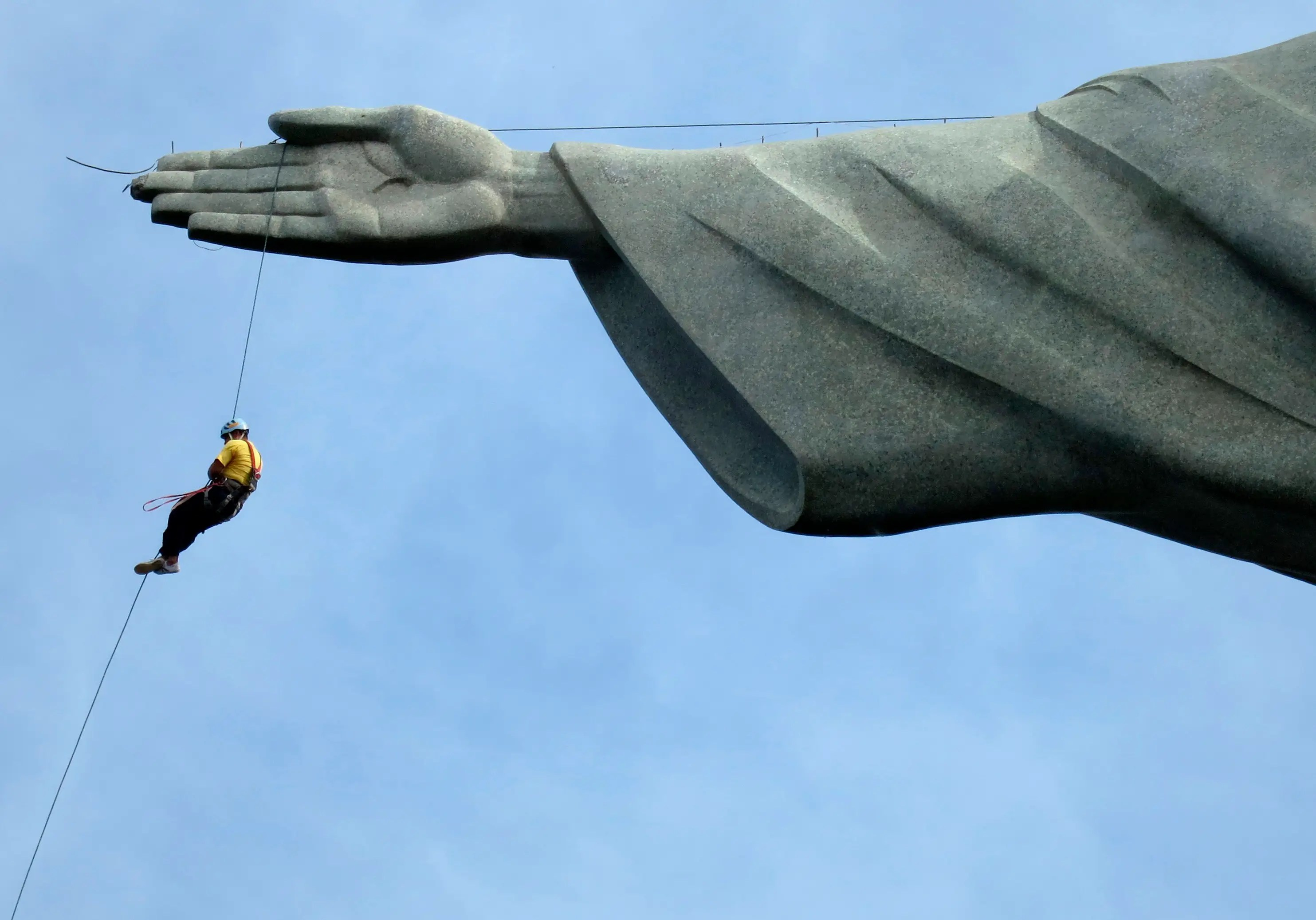 A worker rappels from the Cristo Redentor statue at the Corcovado in Rio de Janeiro.