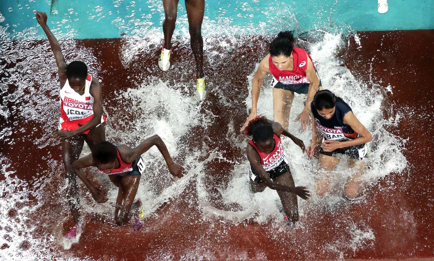 The field races through the water jump in the women's 3000m steeplechase final.