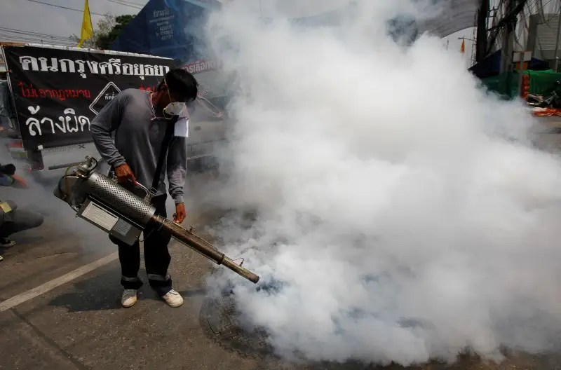 An anti-government protester carries out fumigation to prevent the spread of dengue fever during a rally near the Government Complex in Bangkok February 16, 2014.  REUTERS/Chaiwat Subprasom