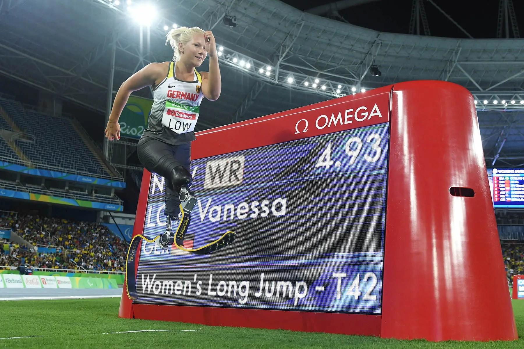 Vanessa Low de Alemania posa delante del marcador de anunciar su récord mundial de salto de longitud de las mujeres.