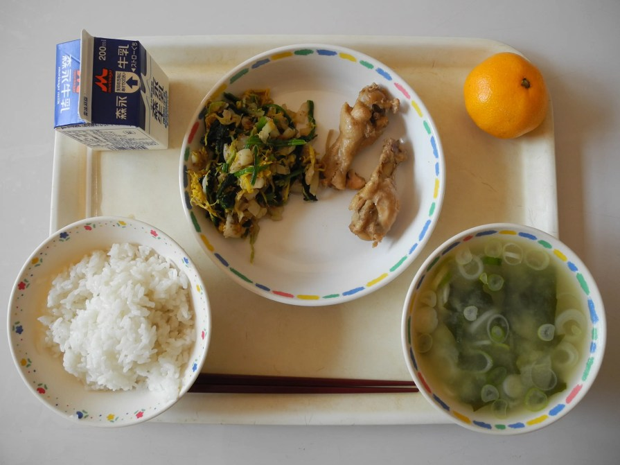 At Jinego Elementary School, in Akita Prefecture, a typical lunch includes chicken, rice, miso wakame soup, vegetable salad, milk, and a tangerine.