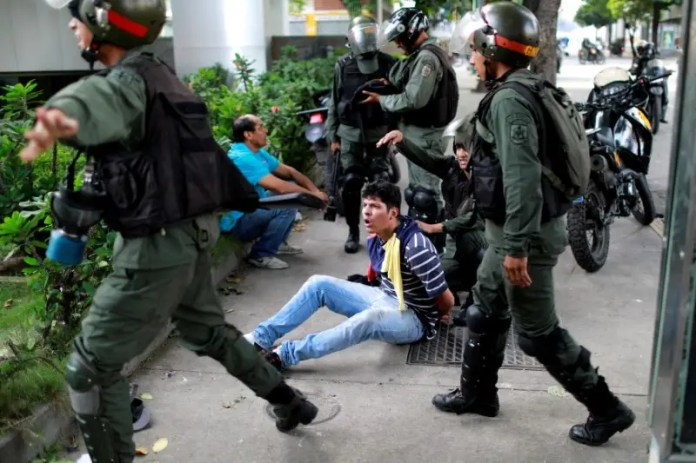 FILE PHOTO: A demonstrator is detained at a rally during a strike called to protest against Venezuelan President Nicolas Maduro's government in Caracas, Venezuela,  July 27, 2017 . REUTERS/Marco Bello/File Photo Trump: 'I'm not going to rule out a military option' for Venezuela Trump: 'I'm not going to rule out a military option' for Venezuela all eyes on venezuela military after protests vote 2017 8