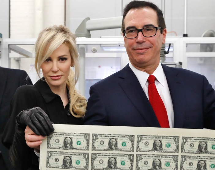 Treasury Secretary Steven Mnuchin, right, and his wife Louise Linton, hold up a sheet of new $1 bills, the first currency notes bearing his and U.S. Treasurer Jovita Carranza's signatures, Wednesday, Nov. 15, 2017,