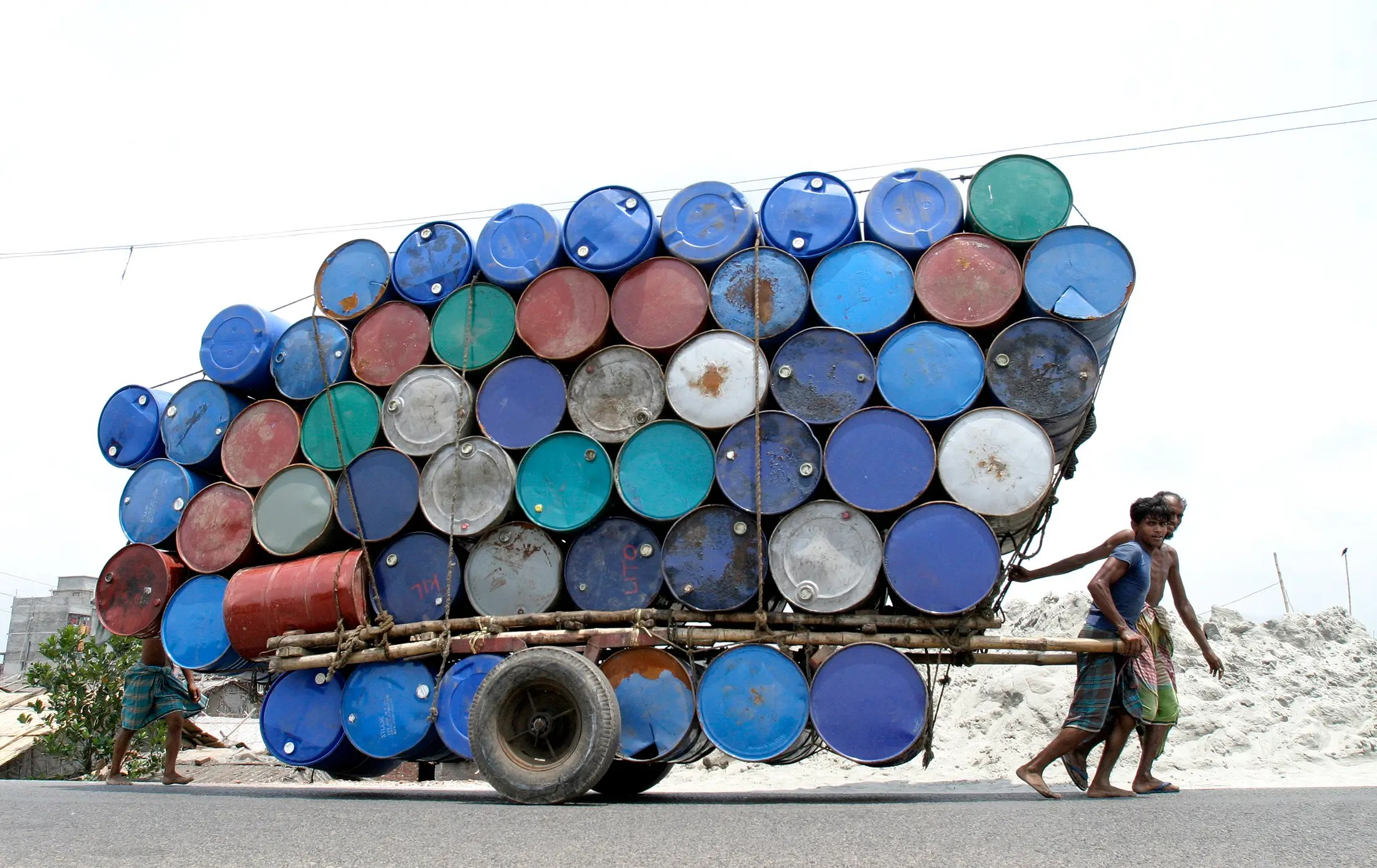 Two people pull a cart of used containers in Dhaka, Bangladesh.