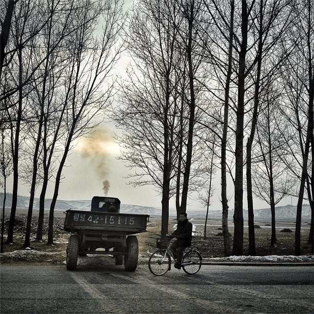 'Tractor, wagon, & bicycle in the North Korean countryside.'
