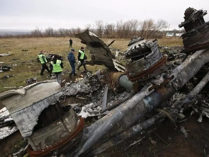 Dutch investigators and an Emergencies Ministry member work at the site where the downed Malaysia Airlines flight MH17 crashed, near the village of Hrabove (Grabovo) in Donetsk region, eastern Ukraine November 16, 2014. REUTERS/Maxim Zmeyev