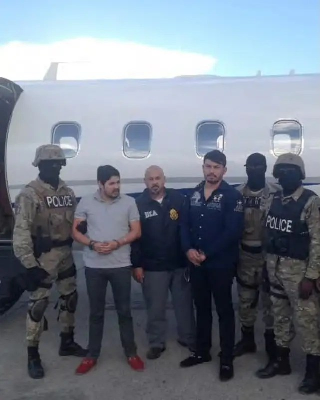 Efrain Antonio Campo Flores (2nd from L) and Franqui Francisco Flores de Freitas stand with law enforcement officers in this November 12, 2015 photo after their arrest in Port Au Prince, Haiti.    Courtesy of U.S. Attorney's Office Manhattan/Handout via REUTERS