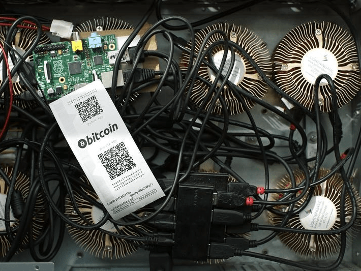 A Bitcoin (virtual currency) mining machine and a paper wallet with QR codes are seen in an illustration picture taken at La Maison du Bitcoin in Paris July 11, 2014.  REUTERS/Benoit Tessier
