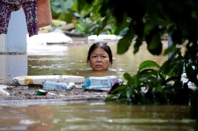 A woman wades through a submerged street at the UNESCO heritage ancient town of Hoi An after typhoon Damrey hits Vietnam November 6, 2017. REUTERS/Kham