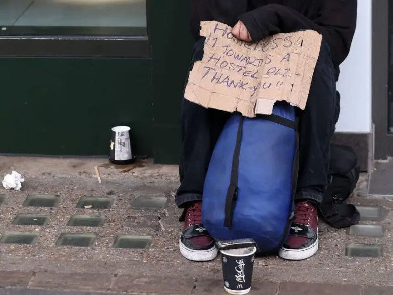 A homeless man sits with a hand-written sign, collecting money from passers-by in central London