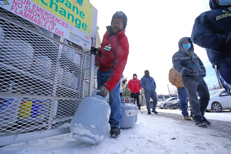 Robert Webster pulls a full canister of propane for sale as customers line up to enter a grocery store Tuesday, Feb. 16, 2021, in Dallas. Even though the store lost power, it was open for cash only sales.