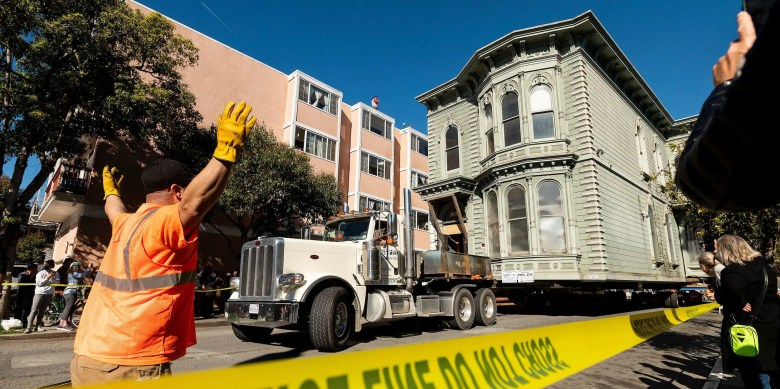 A worker signals to a truck driver pulling a Victorian home through San Francisco on Sunday, Feb. 21, 2021. The house, built in 1882, was moved to a new location about six blocks away to make room for a condominium development. According to the consultant overseeing the project, the move cost approximately $400,000 and involved removing street lights, parking meters, and utility lines.