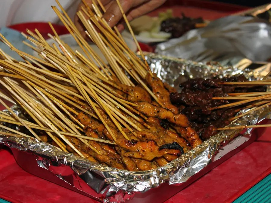 Vendors grill satay — skewers of meat — over an open flame.