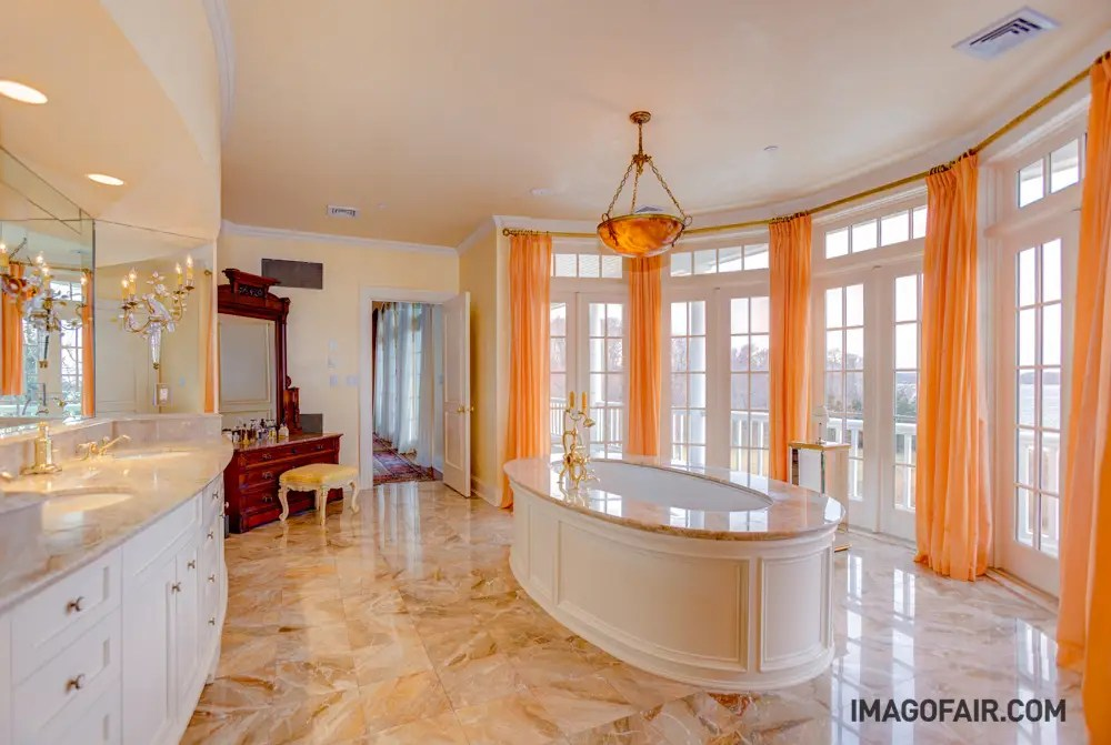 The main house alone has 9 bathrooms. This one includes a double vanity and a dramatic bathtub with smooth marble finishes.