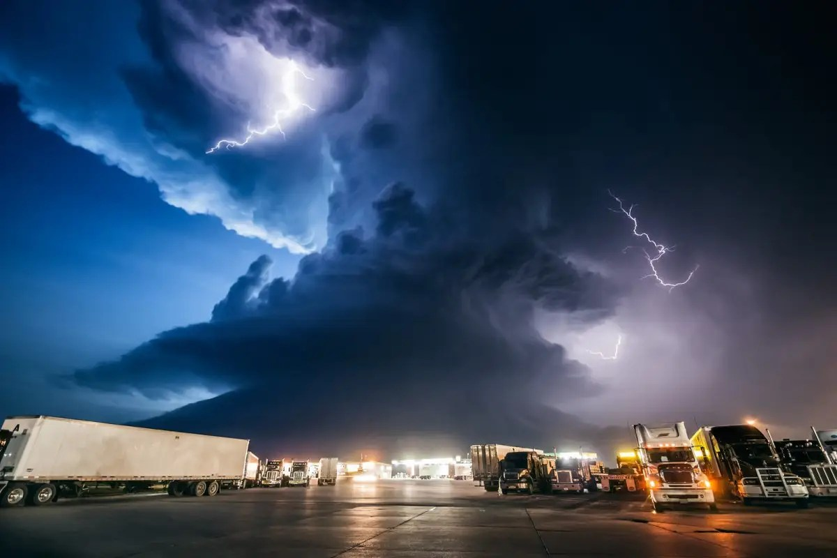 Mike Hollingshead makes a living following the worst storms in America, from snarling tornadoes chewing up the Kansas farmland to supercell thunderstorms massing over the Dakotas. This supercell photograph was taken at a York, Nebraska truck stop after a day of chasing storms.