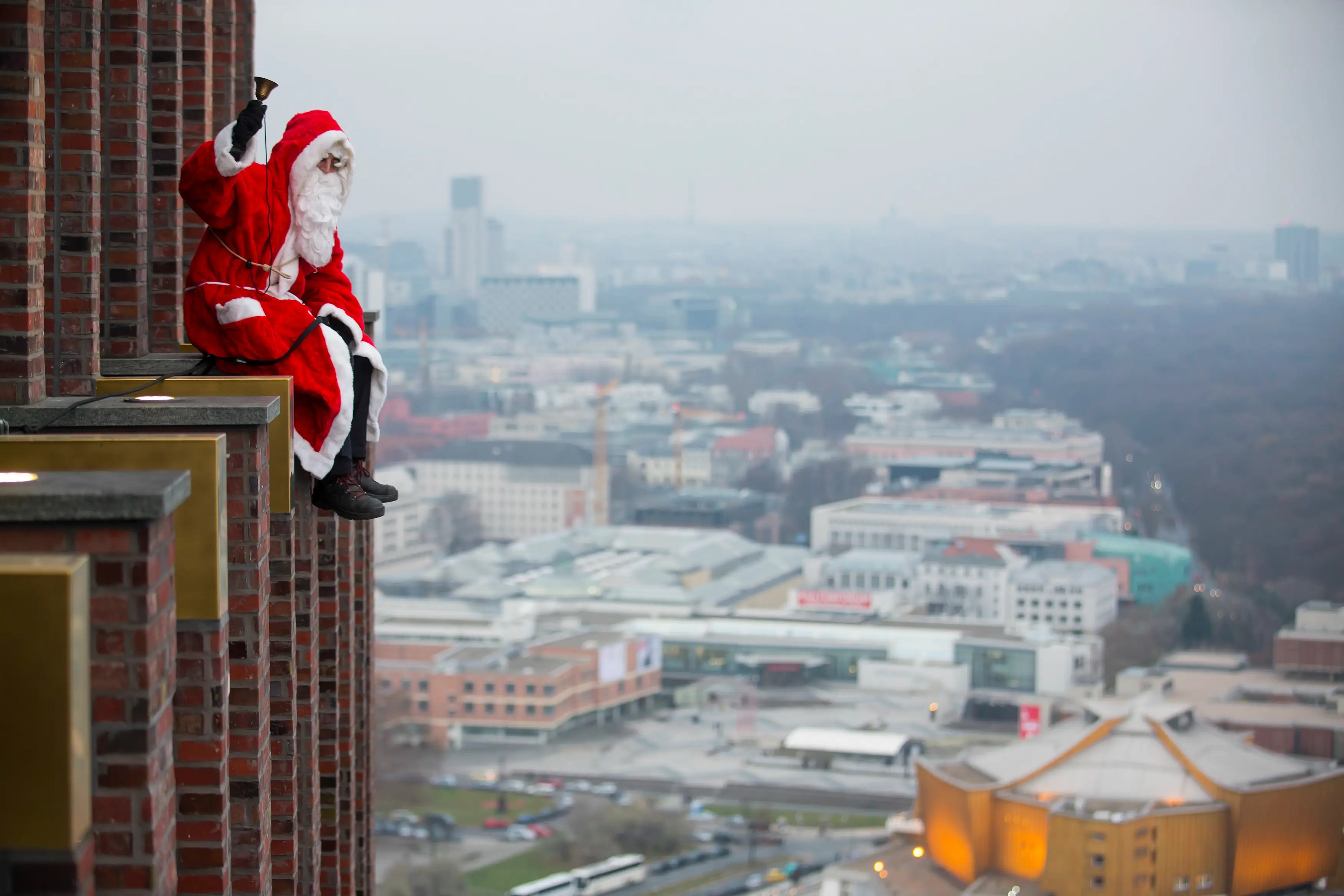 A man dressed as a Santa Claus poses at the front of the Kollhoff Tower at Potsdamer Platz square in Berlin.