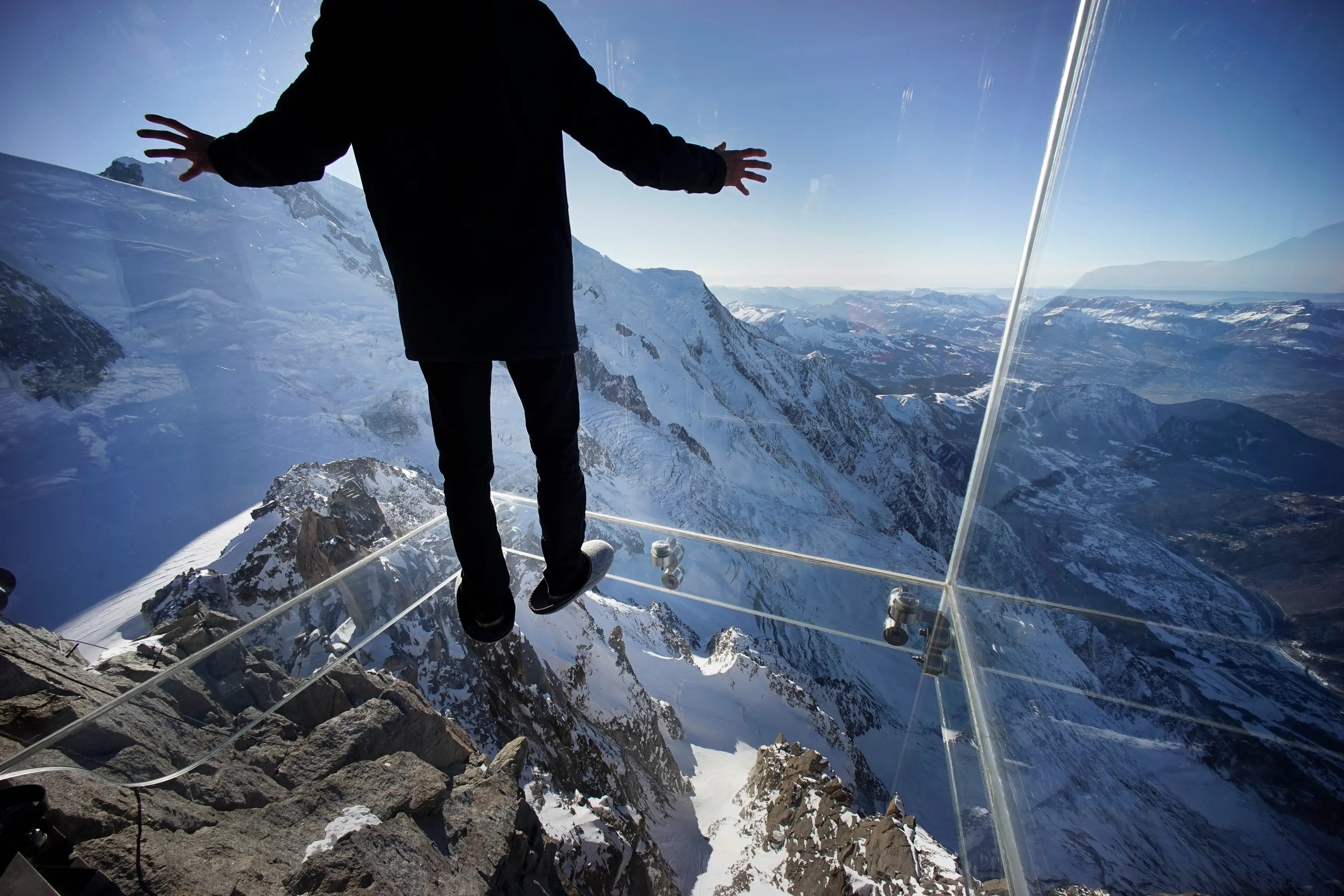 A journalist, wearing slippers to protect the glass floor, stands in the 'Step into the Void' installation during a press visit at the Aiguille du Midi mountain peak above Chamonix, in the French Alps.